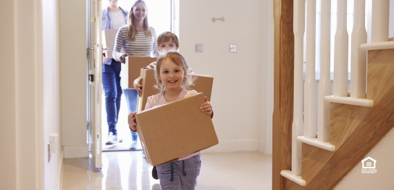 a family carrying boxes in their new home
